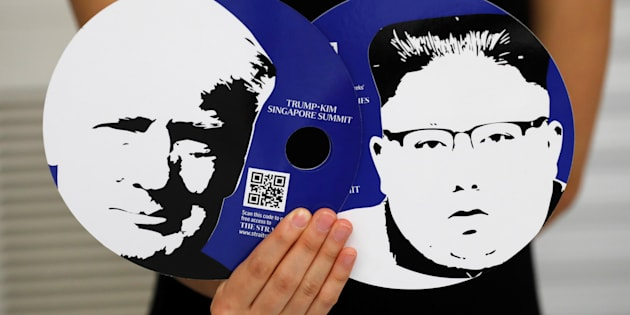A worker of a media center for the summit between the U.S and North Korea shows fans featuring the images of U.S. President Donald Trump (L) and North Korean leader Kim Jong Un,  which provided for journalists in a media kit at the media center in Singapore, June 10, 2018. REUTERS/Kim Kyung-Hoon
