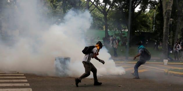 Partidários da oposição entram em confronto com a polícia em protesto contra o presidente Nicolás Maduro em Caracas.
