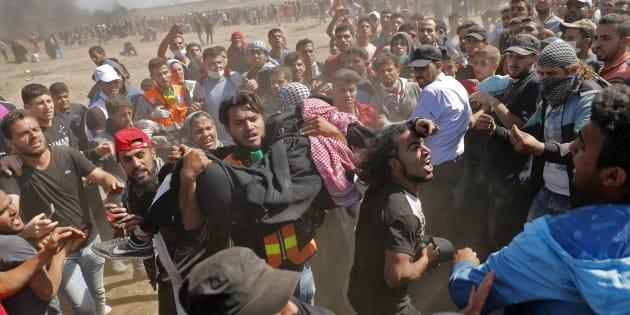 Des Palestiniens lors d'affrontement avec les forces de l'ordre israéliennes près de la frontière de la bande de Gaza, le 14 mai.