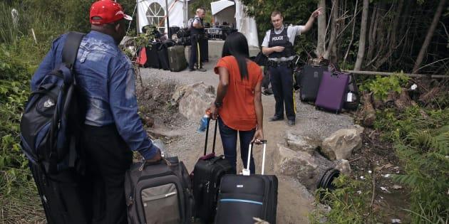 Un agent de la GRC accueille des migrants qui traversent la frontière canado-américaine par le chemin Roxham. Archives.