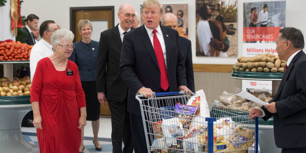 US President Donald Trump pushes a shopping cart as he tours the Church of Jesus Christ of Latter-Day Saints' food distribution center at LDS Welfare Square in Salt Lake City, Utah, December 4, 2017