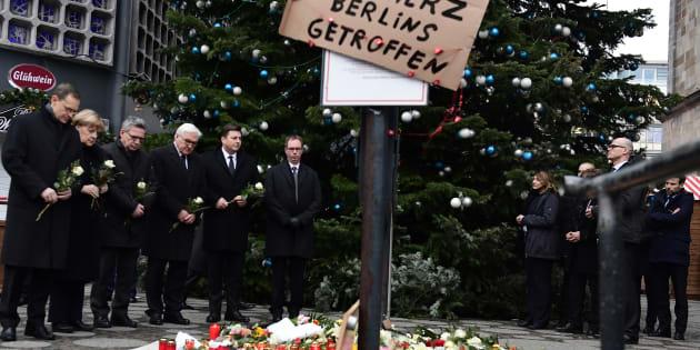"""De gauche à droite, le maire de Berlin Michael Mueller, la chancelière Angela Merkel, le ministre de l'Intérieur Thomas de Maiziere, le ministre des Affaires Etrangères Frank-Walter Steinmeier et le sénateur de Berlin Andreas Geisel apportent des fleurs au mémorial pour les victimes de l'attaque du 19 décembre 2016, devant l'Eglise du Souvenir à Berlin, où un camion a foncé dans la foule d'un marché de Noël. Sur la pancarte on peut lire """"Das Herz Berlins getroffen"""": """"Le coeur de Berlin a été touché""""."""