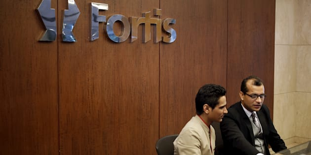 Employees sit on the helpdesk reception of the Fortis Memorial Hospital at Gurgaon.