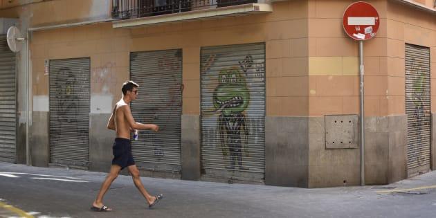 Un turista descamisado pasea por el casco histórico de Palma.