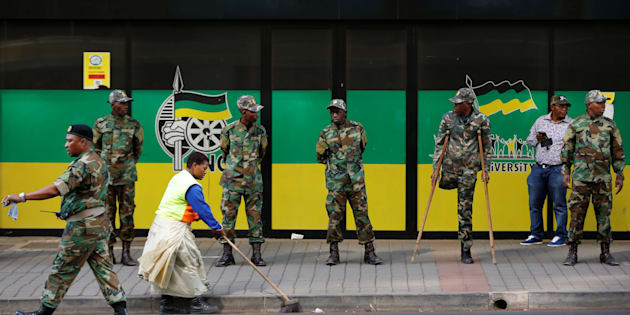 A worker sweeps the street as members of the Umkhonto We Sizwe Military Veterans Association (MKMVA) stand guard at the ANC headquarters in downtown Johannesburg, South Africa, September 5, 2016. REUTERS/Siphiwe Sibeko