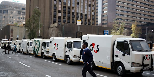 A cash-in-transit worker walks past armoured vehicles parked on the street in Johannesburg during a nationwide protest on June 12 2018, following a spate of deadly heists this year.