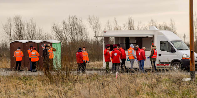 """Des membres de l'association """"La vie active"""" se préparent à accueillir des migrants pour la distribution de repas, le 9 mars à Calais."""