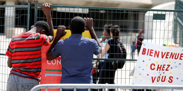 Un jeune réfugié de l'Angola, à gauche, attend son père au stade olympique, lors de la vague des demandeurs d'asile en août dernier.