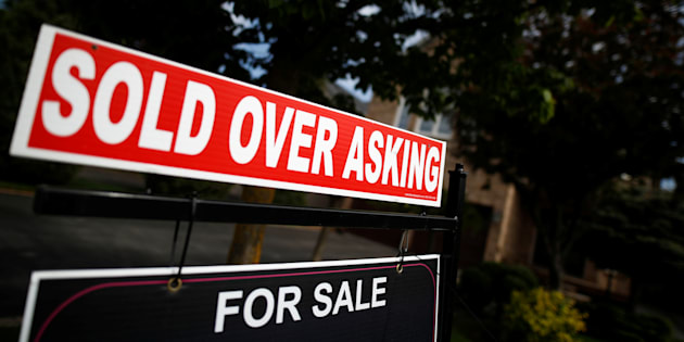A real estate sign stands in front of housing in Vaughan, a suburb in Toronto on May 24, 2017.