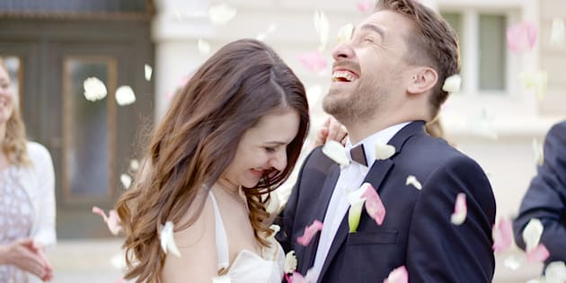 Friends throwing flower petals over bride and groom as they leave church.