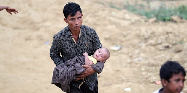 Un réfugié rohingya porte un enfant dans le camp de Palong Khali, à Cox's Bazar, au Bangladesh, le 17 novembre. carries a child in the Palong Khali refugee camp in Cox's Bazar, Bangladesh, November 17, 2017.