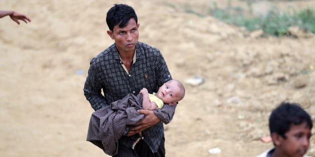 Un réfugié rohingya porte un enfant dans le camp de Palong Khali, à Cox's Bazar, au Bangladesh, le 17 novembre. carries a child in the Palong Khali refugee camp in Cox's Bazar, Bangladesh, November 17, 2017.