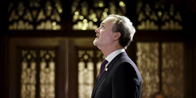 Andre Pratte looks up while waiting in the entrance of the Senate chamber before being sworn-in as a senator on Parliament Hill in Ottawa on April 12, 2016.