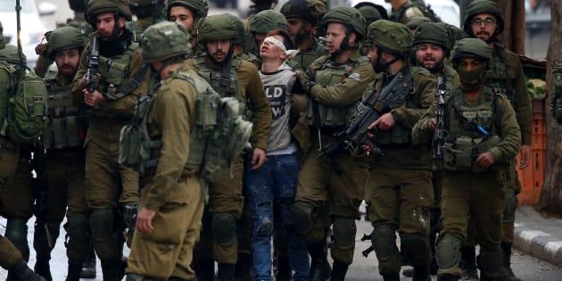 Un grupo de soldados israelíes detienen a Fawzi al-Junaidi, el pasado viernes en las calles de Hebrón.