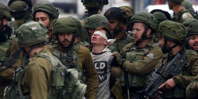 Un grupo de soldados israelíes detienen a un joven manifestante durante unas protestas de hoy en Hebrón, al sur de Cisjordania.
