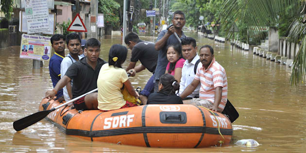 Indian residents navigate floodwaters in the Anilnagar area of Guwahati on July 7, 2016.