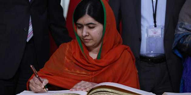 Malala Yousafzai signs a guest book at Parliament Hill in Ottawa.