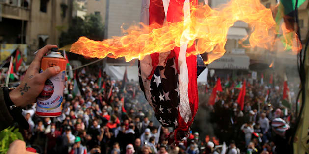 Protesters set a U.S flag on fire near the U.S. embassy in Awkar north of Beirut, Lebanon December 10,2017.
