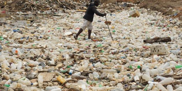 A man walks between plastics bottles in a river near Abidjan in Ivory Coast on May 23, 2017. / AFP PHOTO / ISSOUF SANOGO        (Photo credit should read ISSOUF SANOGO/AFP/Getty Images)