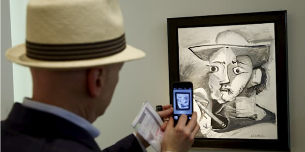 """A man takes a picture of the painting """"Le peintre au chapeau"""" (a painter with hat) by late Spanish artist Pablo Picasso."""