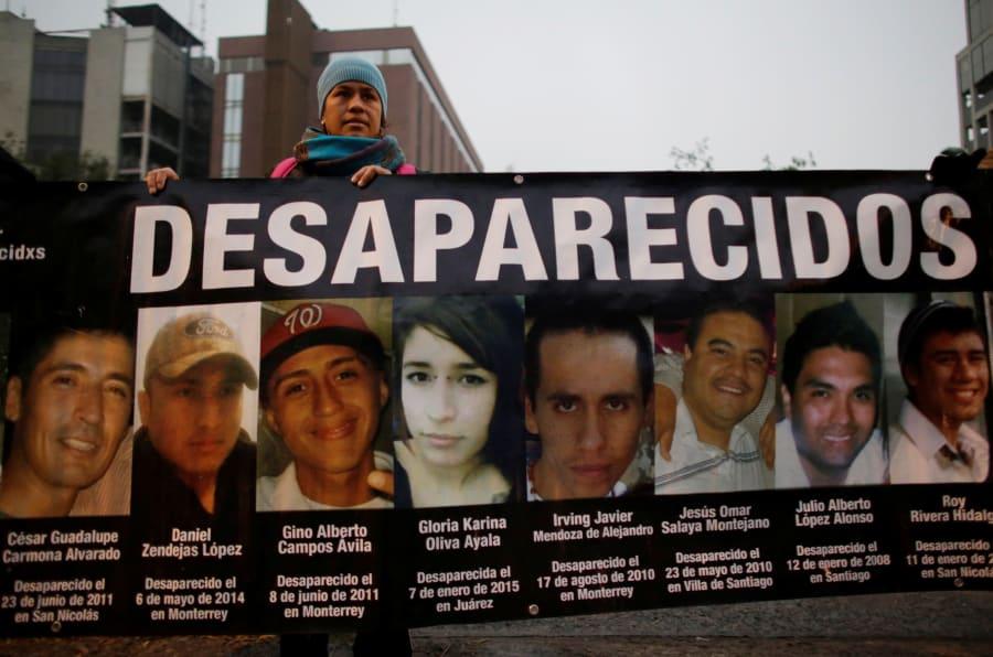 Un manifestante sostiene una pancarta con imágenes de su pariente y otras personas, que según dijeron desaparecieron o fueron asesinadas, durante una manifestación que exigía justicia para las víctimas de la violencia, en Monterrey, Nuevo León, México, el 10 de diciembre de 2016.