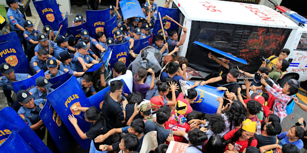 Activists and Indigenous People's groups clash with anti-riot policemen in front of the U.S. Embassy in Manila.