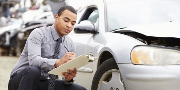 Loss adjuster inspecting car involved in accident.