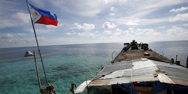 """A Philippine flag flutters from BRP Sierra Madre, a dilapidated Philippine Navy ship that has been aground since 1999 and became a Philippine military detachment on the disputed Second Thomas Shoal, part of the Spratly Islands, in the South China Sea March 29, 2014.  REUTERS/Erik De Castro/File Photo  FROM THE FILES PACKAGE - SEARCH """"SOUTH CHINA SEA FILES"""" FOR ALL IMAGES"""