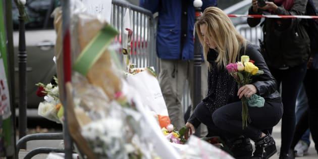 Imagen de archivo de una mujer dejando flores en París en recuerdo de las víctimas de los atentados de noviembre de 2015.