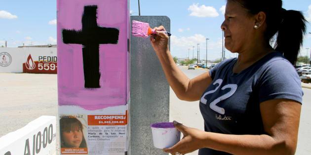 Una mujer pinta una cruz con rosa y negro, los colores usados para denunciar un feminicidio.