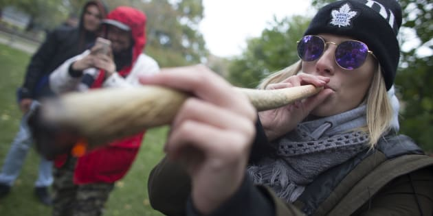 A woman smokes a somewhat oversized marijuana cigarette during a legalization party at Trinity Bellwoods Park, Toronto, Ont., Oct. 17, 2018.