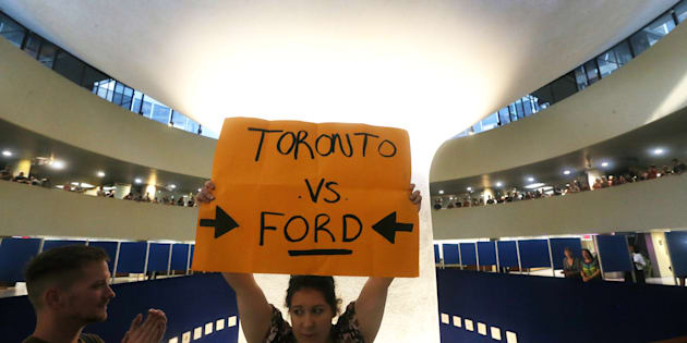 Protesters gather in the Toronto City Hall rotunda after an emergency motion pertaining to Premier Doug Ford's plan to cut city council down to 25 seats from the 47 seats on July 27, 2018.