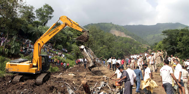 Heavy machinery removes debris as rescue personnel search for survivors and bodies of victims after a landslide along a highway at Kotrupi, some 200 kilometres (124 miles) from Himachal Pradesh state capital Shimla.