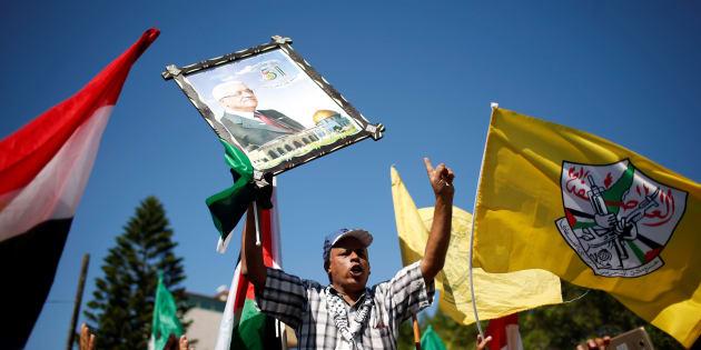 Un homme portant le portrait de Mahmoud Abbas après l'annonce de l'accord entre le Fatah et le  Hamas, à Gaza, le 12 octobre 2017.