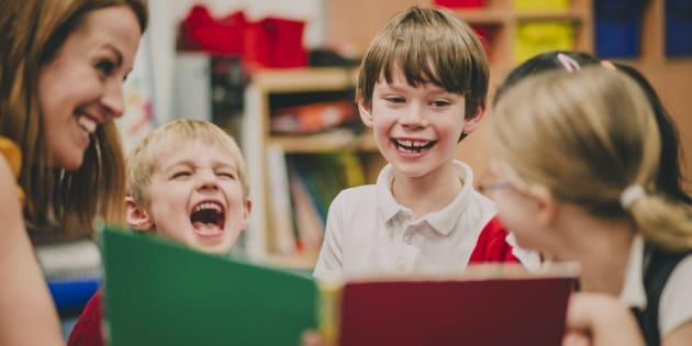 Niños contentos leyendo con su maestra.