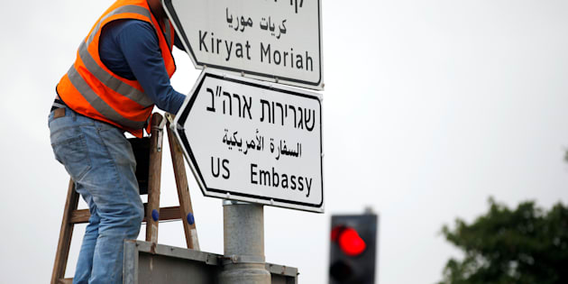 A worker hangs a road sign directing to the U.S. embassy, in the area of the U.S. consulate in Jerusalem, May 7, 2018. REUTERS/Ronen Zvulun