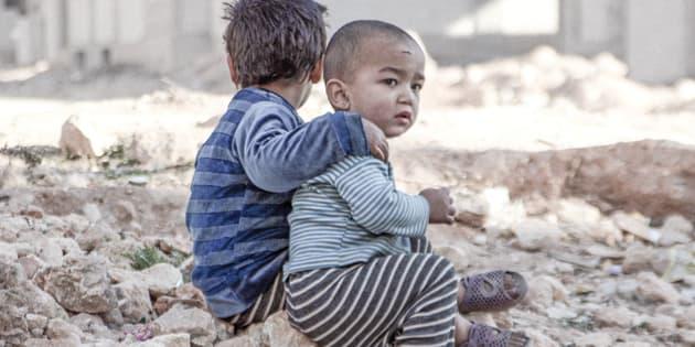 Esraa, de cuatro años y su hermano Waleed, de tres, sentados a las afueras de un centro de desplazados, tras escapar de Alepo (Siria).