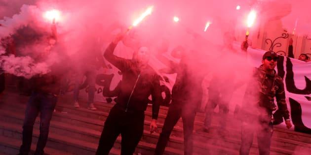 Varios hombres con bengalas durante una protesta nocturna en Túnez.