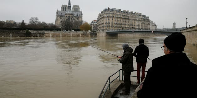 Two men fish on the flooded banks of the River Seine in Paris, France, after days of almost non-stop rain caused flooding in the country, January 27, 2018. REUTERS/Pascal Rossignol