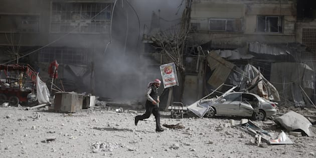 A man runs on rubble of damaged buildings after an airstrike in the besieged town of Douma in eastern Ghouta in Damascus, Syria, February 7, 2018. REUTERS/ Bassam Khabieh