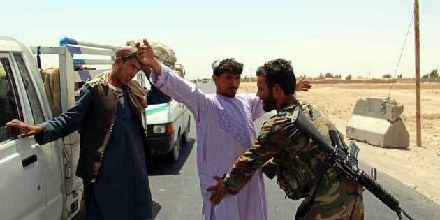Un soldado registra a un ciudadano en un control en el distrito de Maiwind, en Kandahar (Afganistán), después del atentado contra los soldados.