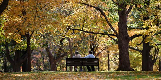 People sit on a bench on a warm autumn day at Rideau Hall in Ottawa, Oct. 23, 2017.