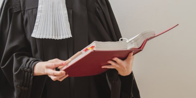 canadian lawyer in toga, reading from a red law book