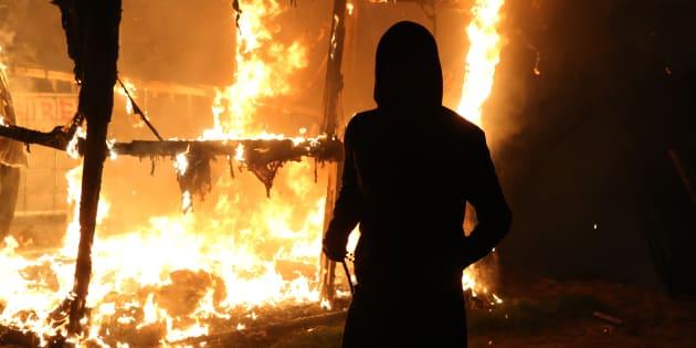 Un migrant devant l'incendie d'une cabane dans la nuit du mardi 25 au mercredi 26 octobre
