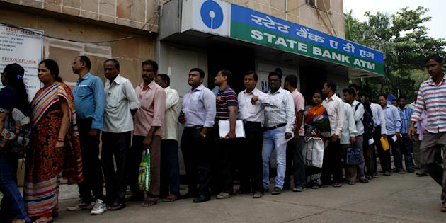 People stand in the queue to enter into the bank to withdraw money and exchange the discontinued notes.