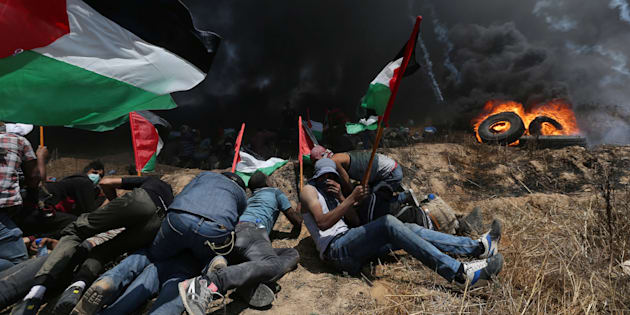 Palestinian demonstrators take cover from Israeli fire and tear gas during a protest against U.S. embassy move to Jerusalem and ahead of the 70th anniversary of Nakba, at the Israel-Gaza border in the southern Gaza Strip May 14, 2018. REUTERS/Ibraheem Abu Mustafa