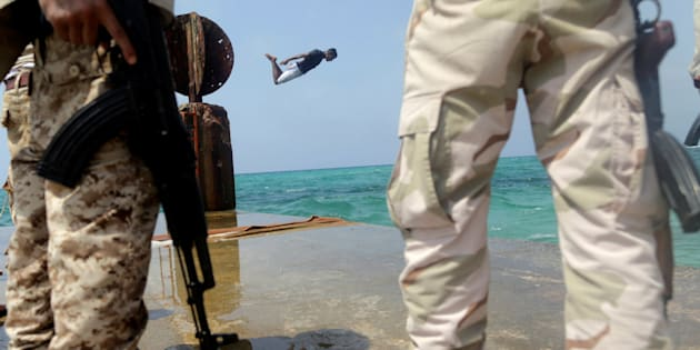 A man jumps into the sea as memebrs of Libyan National Army stand guard in Sabri, a central Benghazi district, Libya, August 12, 2017. Picture taken August 12, 2017. REUTERS/Esam Omran Al-Fetori