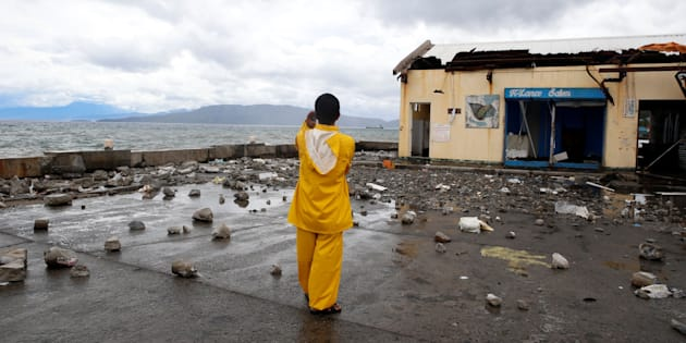 A port worker stands amidst debris swept from the sea at the height of Typhoon Nock Ten in Mabini, Batangas, in the Philippines December 26, 2016. (REUTERS/Erik De Castro)
