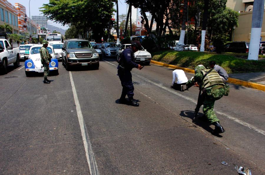 ACAPULCO, GUERRERO, 26ABRIL2018.- Soldados y policías buscan casquillos percutidos, luego de que un hombre robara un taxi en la costera Miguel Alemán, frente al centro comercial Galerías Acapulco, desatándose una persecución a balazos entre el ladrón del taxi y presuntos escoltas.