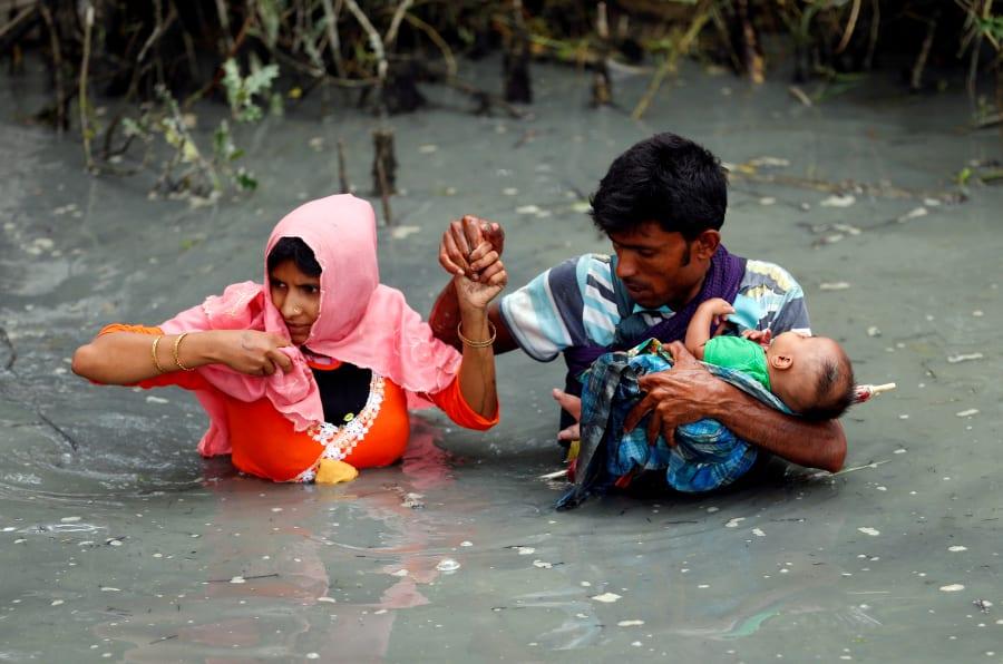 Una pareja de refugiados rohingyas y su bebé cruzan el río Naf en Teknaf, Bangladesh.